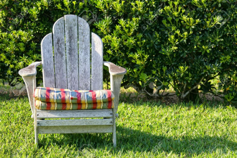9746893-An-old-weathered-Adirondack-chair-in-the-garden-with-a-hedge-as-a-backdrop--Stock-Photo